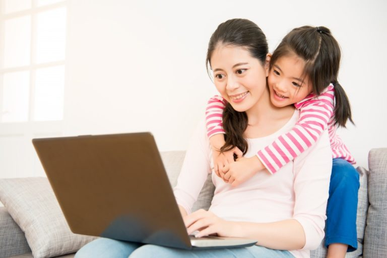 mom and kid watching at a laptop