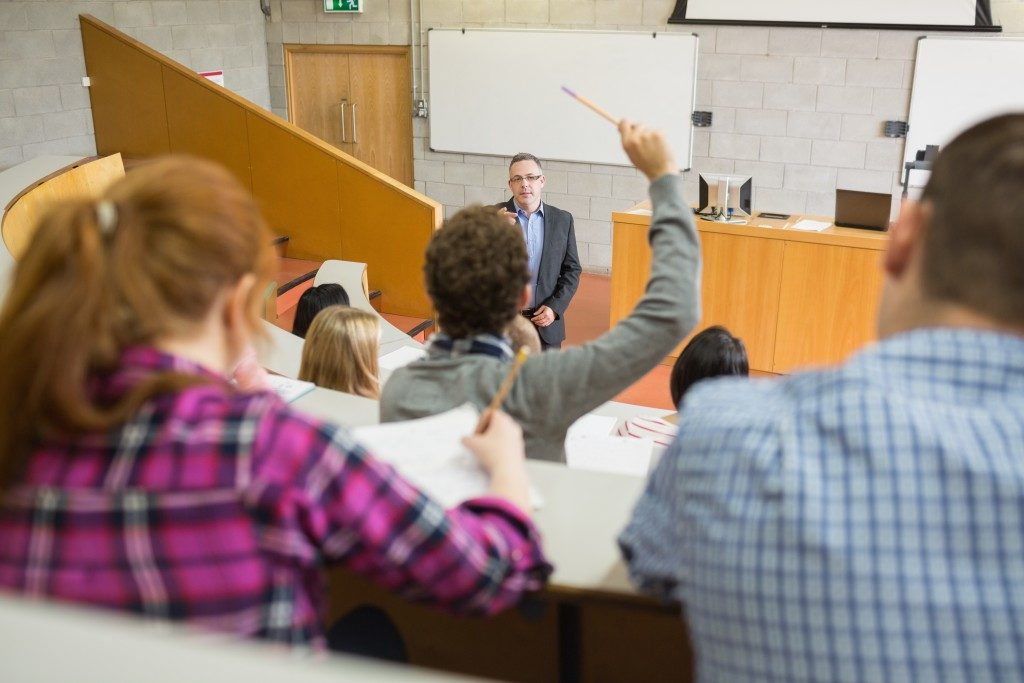 Person raising his hand in class