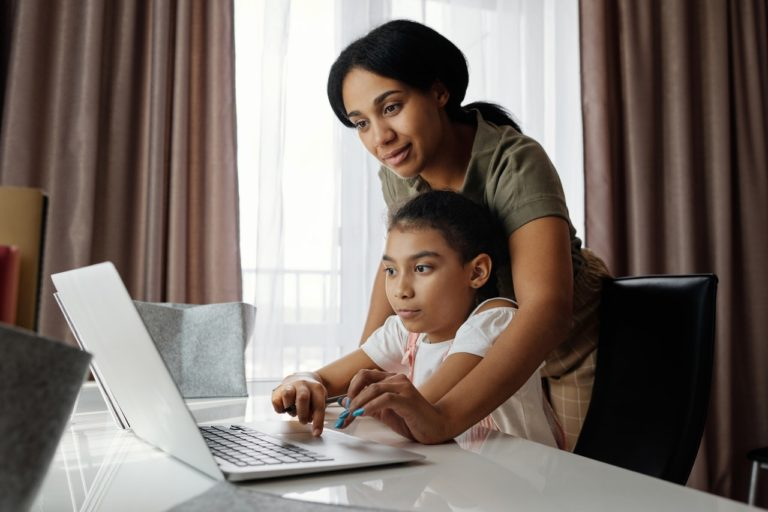 parent helping daughter with online school